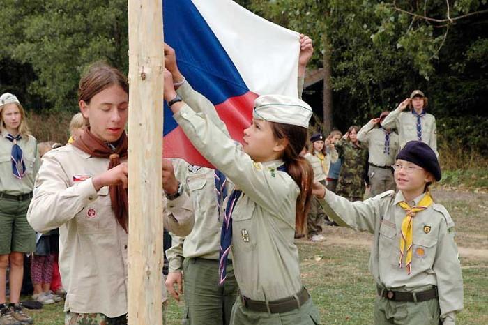 marek-sychra-komar-z-35-brnenskeho-oddilu-junaka-a-nikola-volfova-hopik-z-39-brnenskeho-oddilu-svazu-skautu-a-skautek-cr-pri-slavnostnim-zaverecnem-nastupu-spousti-statni-vlajku